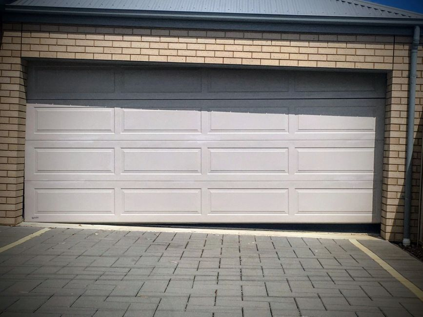 A white garage door with a gap at the bottom right hand side.